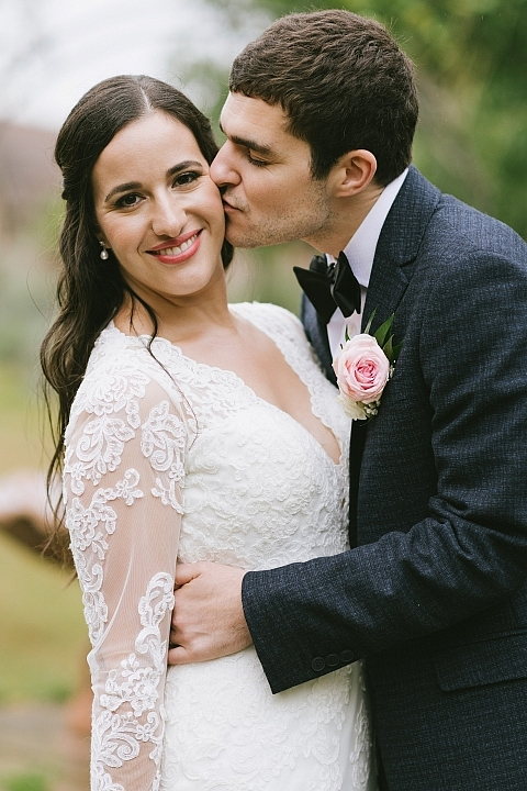 Bride looking at the camera while groom kissed her on the cheek